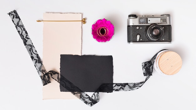 Set of papers near fresh flower with rings on plate, retro camera and tape