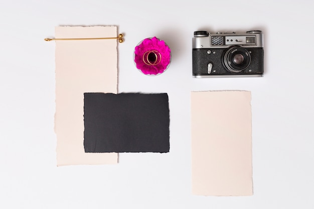 Set of papers near fresh flower with rings on plate and retro camera