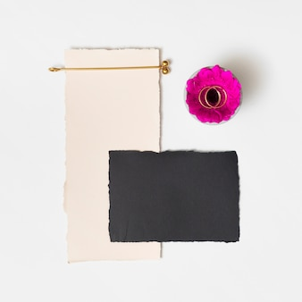 Set of papers near fresh flower with rings on plate