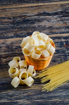 Set of pasta and spaghetti and macaroni in a bucket on a dark wooden background. high angle view.