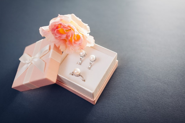 Set of pearl jewellery in gift box with flowers. silver earrings and ring with pearls as a present for holiday.