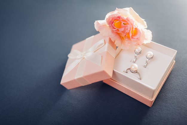 Set of pearl jewellery in gift box with flowers. silver earrings and ring with pearls as a present