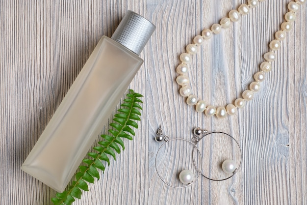 A set of pearl and necklace earrings next to a green branch and perfume.