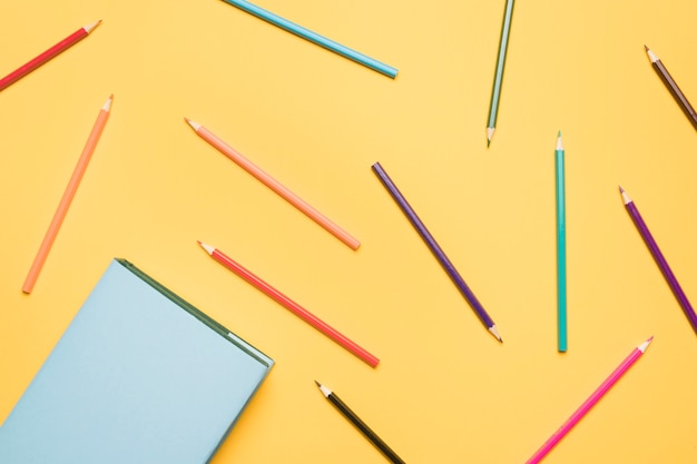 Set of pencils scattered on yellow background