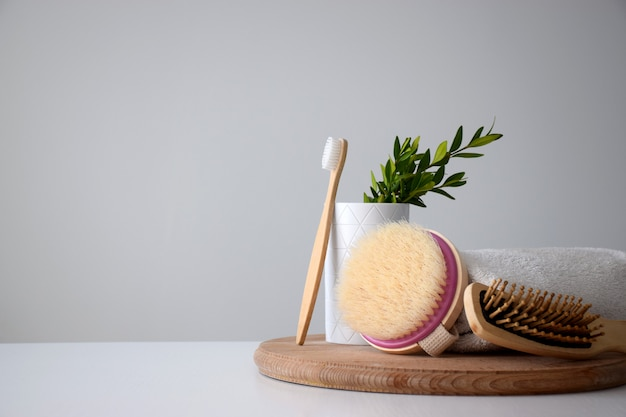 Set of personal eco accessories: tooth brush, body brush, hairbrush and white towel on wooden round board