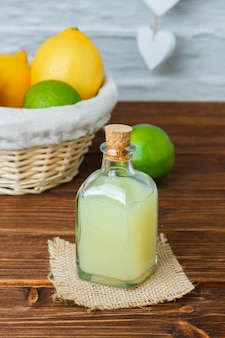 Set of on piece of white cloth and lemon and juice in a basket on a wooden surface. high angle view.