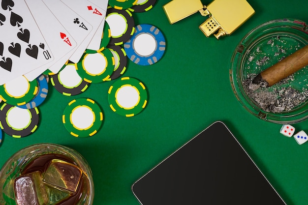 Set to playing poker with cards and chips on green table. view from above with copy space. banner template layout mockup for online casino. green table, top view on workplace.