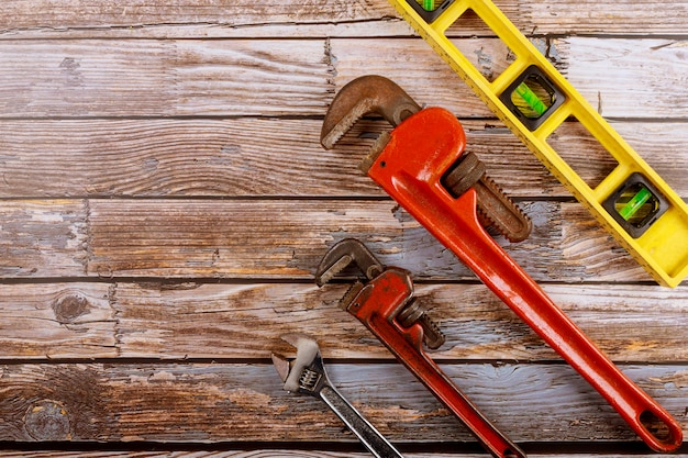 Set plumbing adjustable wrench with construction level on wooden board.