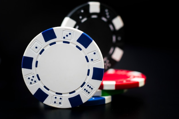 Set of poker chips of different colors on a black background.