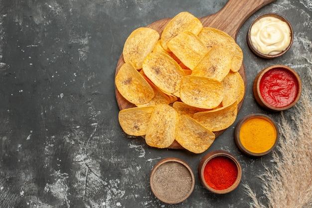 회색 테이블 푸티 지에 다양한 향신료 마요네즈와 케첩이 들어있는 감자 칩을 설정하십시오.