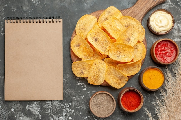 Set potato chips containing different spices mayonnaise and ketchup on gray table