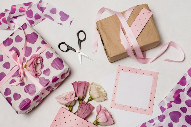Set of present boxes near flowers, papers and scissors