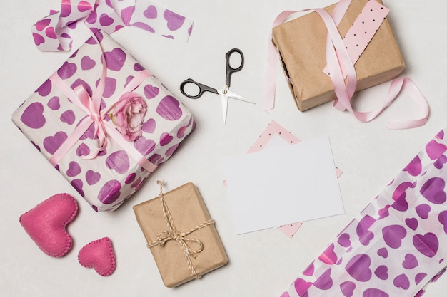 Set of present boxes near papers, hearts and scissors