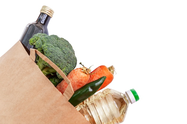 A set of products in a paper eco bag in the corner of the frame. mix of fresh vegetables. delivery during the coronavirus pandemic. isolated on a white background. space for text.