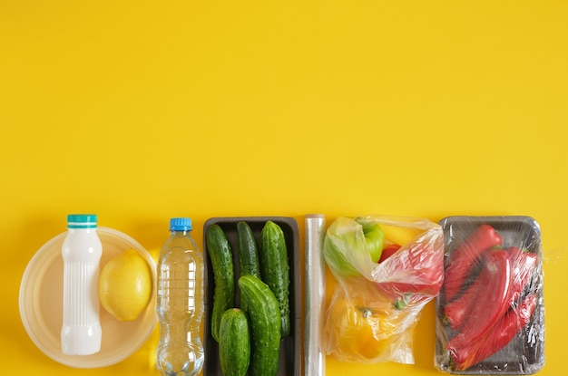 Set of products in various plastic packaging, plastic environmental pollution concept, say no to plastic, yellow background copy space top view