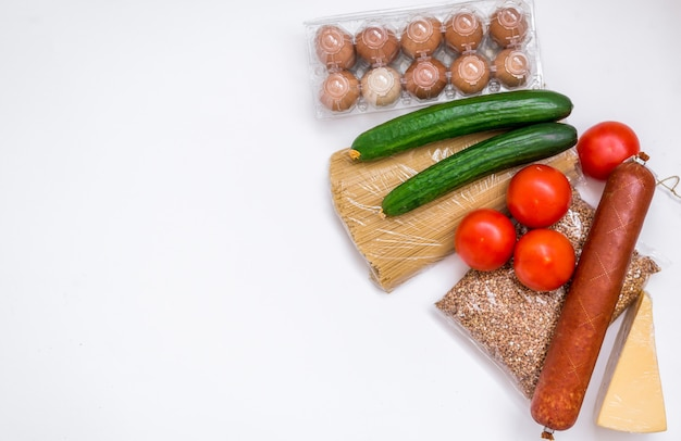 A set of products on a white background. groceries, vegetables, butter, eggs and sausage. food package