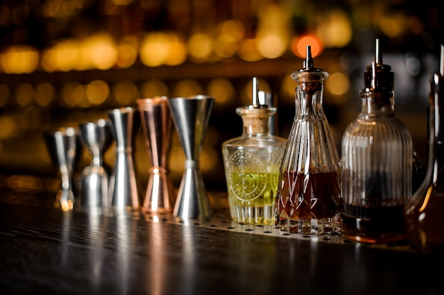Set of professional barman tools including jiggers and little bottles with liquor