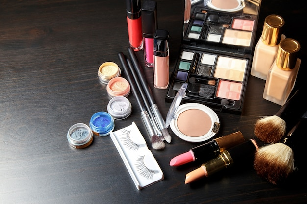 Set professional cosmetics on dark background with copy space
