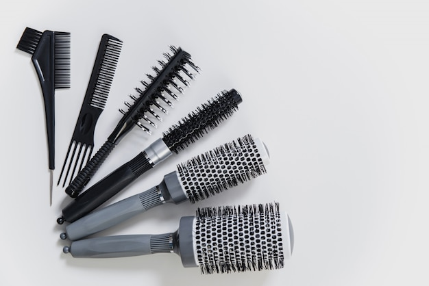 Set of professional hairbrushes on white background in hair salon
