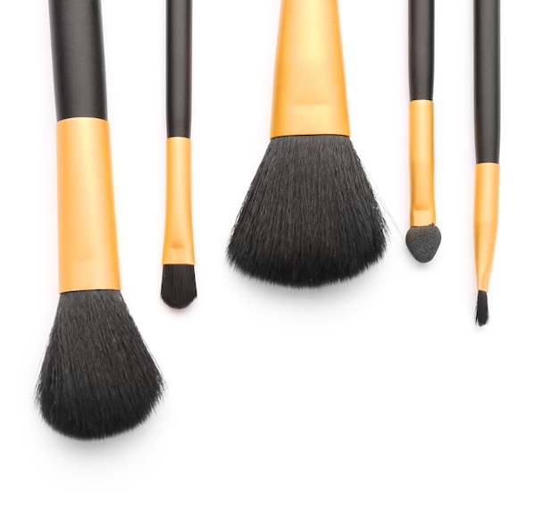Set of professional makeup brushes on white background