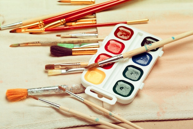 Set of professional watercolor artist brushes in a hand made roll case and watercolor paints close up