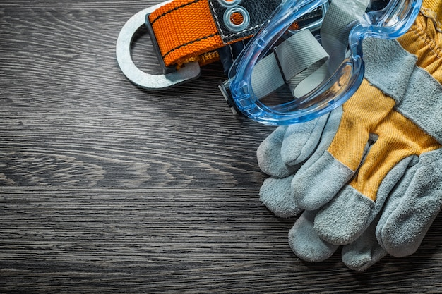 Set of protective gloves belt glasses on wooden board
