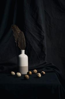 Set di uova di quaglia vicino a piume in vaso