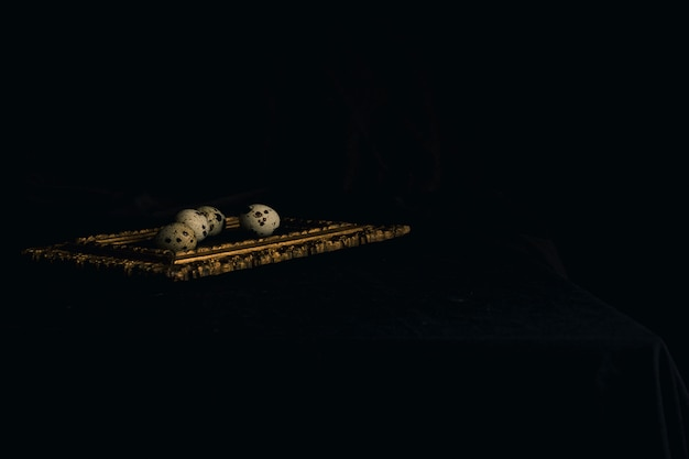 Set of quail eggs on photo frame between blackness
