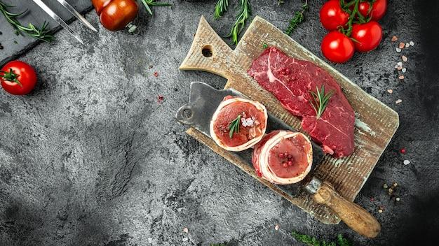 Поставьте стейк из сырой говядины на темный стол. стейк из говяжьего огузка, филе вырезки миньон для гриля. формат длинного баннера, вид сверху.