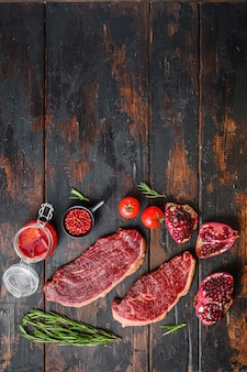 Set of raw picanha beef steaks with seasoning, rosemary, tpmators, spicy chili oil and pomegranates over old dark wood table, top view with space for text.