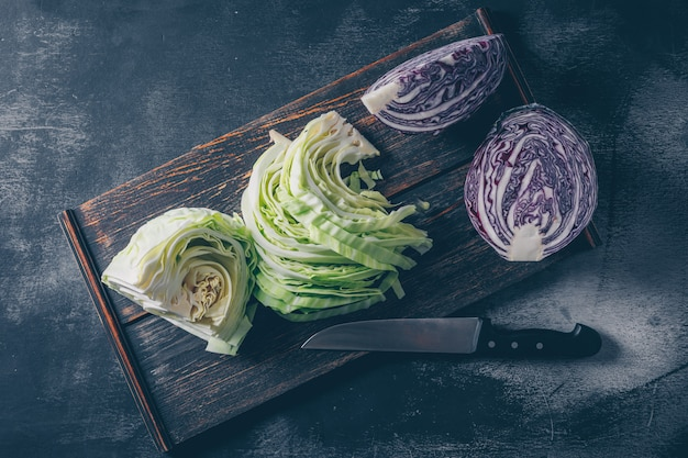 Set of red cabbage and knife and sliced and chopped cabbage in a cutting board on a dark textured background. top view.