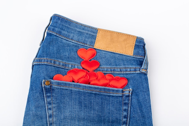Set of red hearts in blue jeans pocket on white