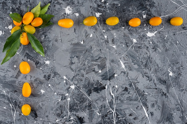 Set di kumquat maturi con foglie verdi su sfondo marmo.