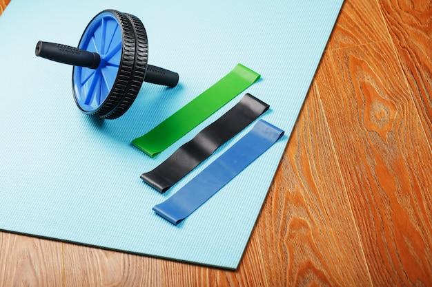 Set of roll for body muscles and elastic bands for fitness on a blue training mat