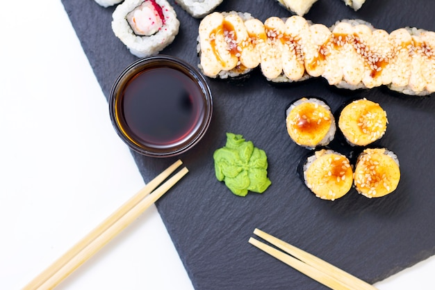 Set of rolls, sauce and wooden sticks on a stone black table. top view with copy space.