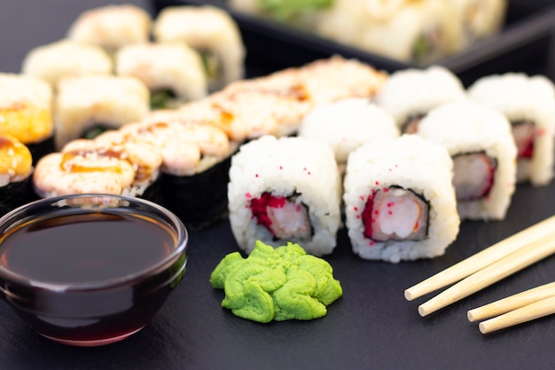 Set of rolls, wasabi, sauce and wooden sticks on a stone black table.