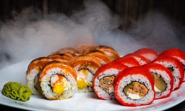Set of rolls on a white plate with wasabi and smoke