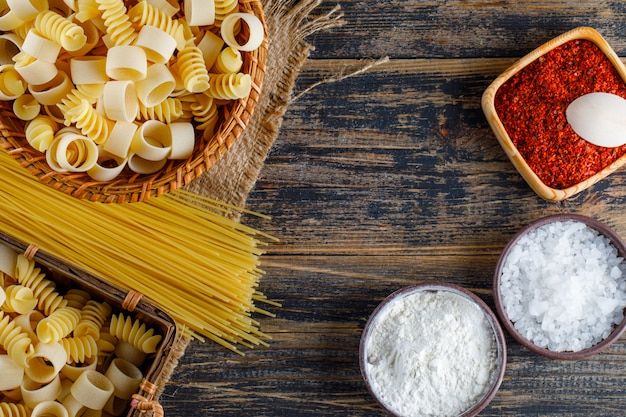 Set of salt, red spice, spaghetti and macaroni pasta on a wooden background. flat lay.