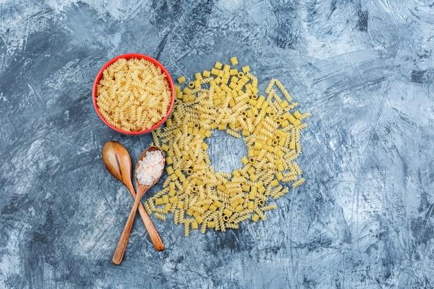 Set di sale in cucchiaio di legno e pasta assortita in una ciotola su uno sfondo di gesso grungy. laici piatta.
