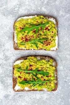 朝食にサンドイッチをセット-全粒粉のダークパンのスライス、クリームチーズ、ワカモレ、飾り