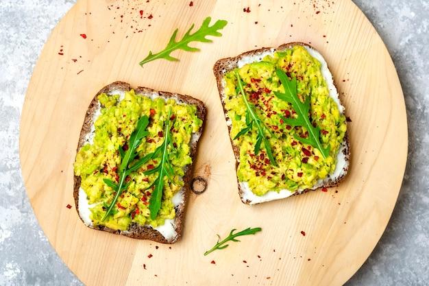 朝食にサンドイッチをセット-全粒粉の暗いパンのスライス、コンクリートのテーブルにワカモレ