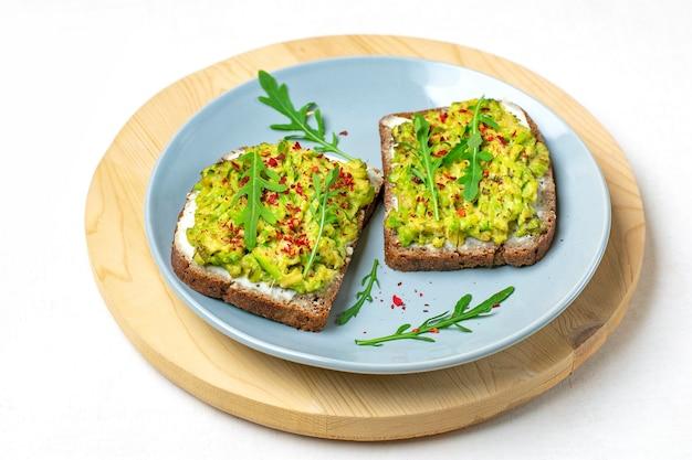 朝食にサンドイッチをセット-全粒粉の暗いパンのスライス、白い背景にワカモレ
