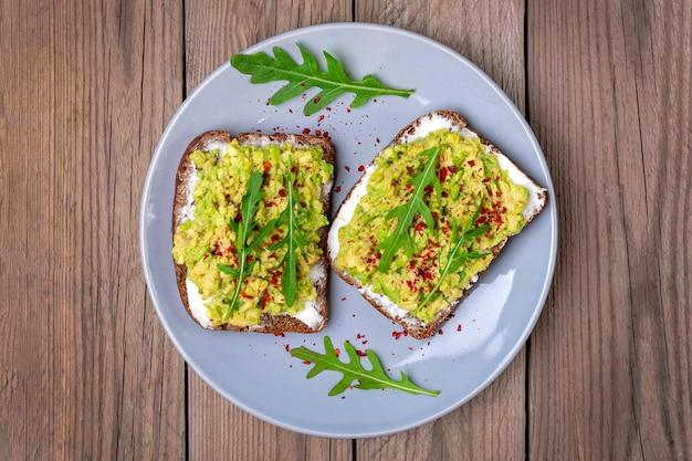 朝食にサンドイッチをセット-全粒粉の暗いパンのスライス、木製のテーブルにワカモレ