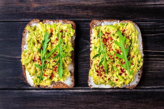 木製のテーブルにワカモレと全粒粉の暗いパンの朝食スライスのサンドイッチを設定します