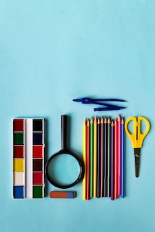 A set of school supplies. magnifying glass, pencils, ruler, sheath, watercolor on a blue paper background with space for text.