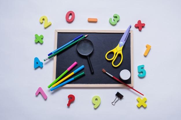 A set of school supplies on a slate