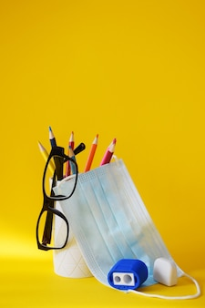 Set of school supplies on yellow table: pencils, glasses, sharpener, eraser and medical protective mask