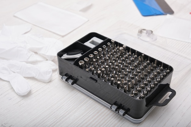 Set of screwdriver bits in a black box, gloves, tools for replacing the glass of the phone and tablet