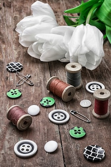 Set of sewing accessories from threads and buttons on the background of white tulips