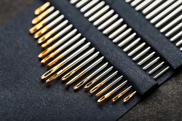 A set of sewing needles on a black background.